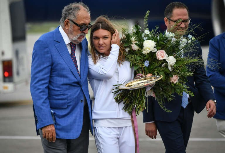 Simona Halep et al. standing next to a person: Simona Halep will not defend her 2019 Wimbledon singles title due to a calf injury
