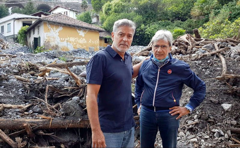 George Clooney standing in front of a rock: MEGA