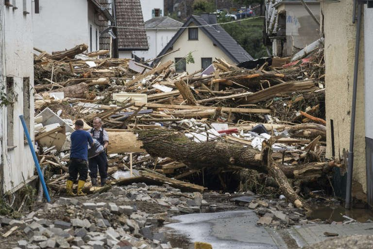 a person standing next to a pile of hay: Streets in towns like Germany's Schuld are choked with debris from the sudden floods