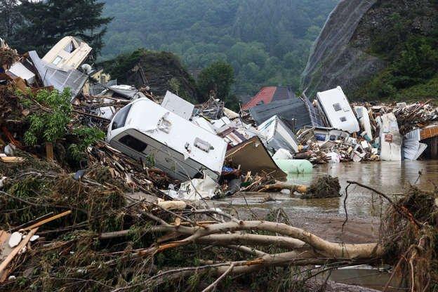Slide 1 of 28: A pile of broken trees and debris is seen in a flooded area following heavy rainfall in Kreuzberg, Germany, on July 17, 2021.