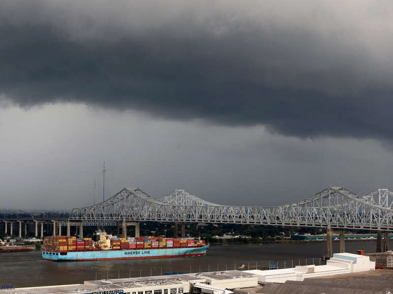 """a large ship in a body of water: The """"Sealand Illinois,"""" a Hong Kong registered cargo ship, passes under the Crescent City Connection Bridge on the Mississippi River in New Orleans, Tuesday, Aug. 13, 2019. AP Photo/Gerald Herbert"""