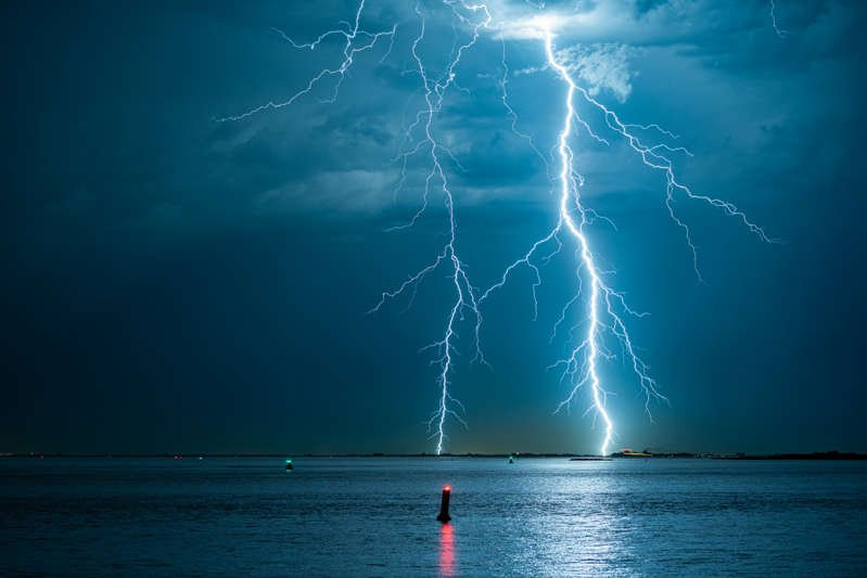 a large body of water: File photo of a branched lightning bolts strike down near the coast.