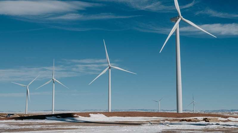 a windmill next to a body of water: A wind farm in Carbon County, Wyo. Clean energy is among the areas that would see investment under President Biden's infrastructure plan.